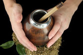 Woman hands holding calabash and bombilla with yerba mate isolated on black — Stock Photo