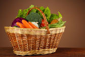 Different vegetables in basket on table on brown background — Stock Photo