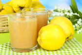 Sweet quince with juice on table on light blue background — Stock Photo