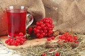 Red berries of viburnum on stand with cup of tea on table on sackcloth background — Stockfoto