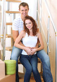 Young couple sitting on stairs in new house — Stock Photo