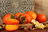 Ripe persimmons with nuts on table on wicker background — Stock Photo
