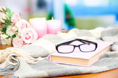 Composition with old book, eye glasses, candles, flowers and plaid — Stock Photo