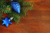 Beautiful Christmas decorations on fir tree on wooden background — Foto de Stock
