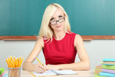 学校的老师在黑板背景上坐在桌旁 — 图库照片