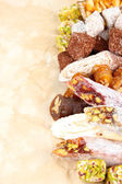 Tasty oriental sweets, on brown background — Stock Photo