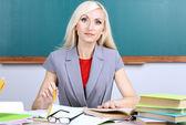 School teacher verifies homework on blackboard background — Stock Photo