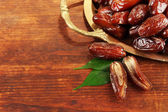 Dried dates on metal tray on wooden background — Stock Photo