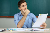 Young teacher review tests in school classroom — Stock Photo