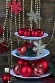 Decorazioni natalizie su dessert stanno, su fondo in legno — Foto Stock