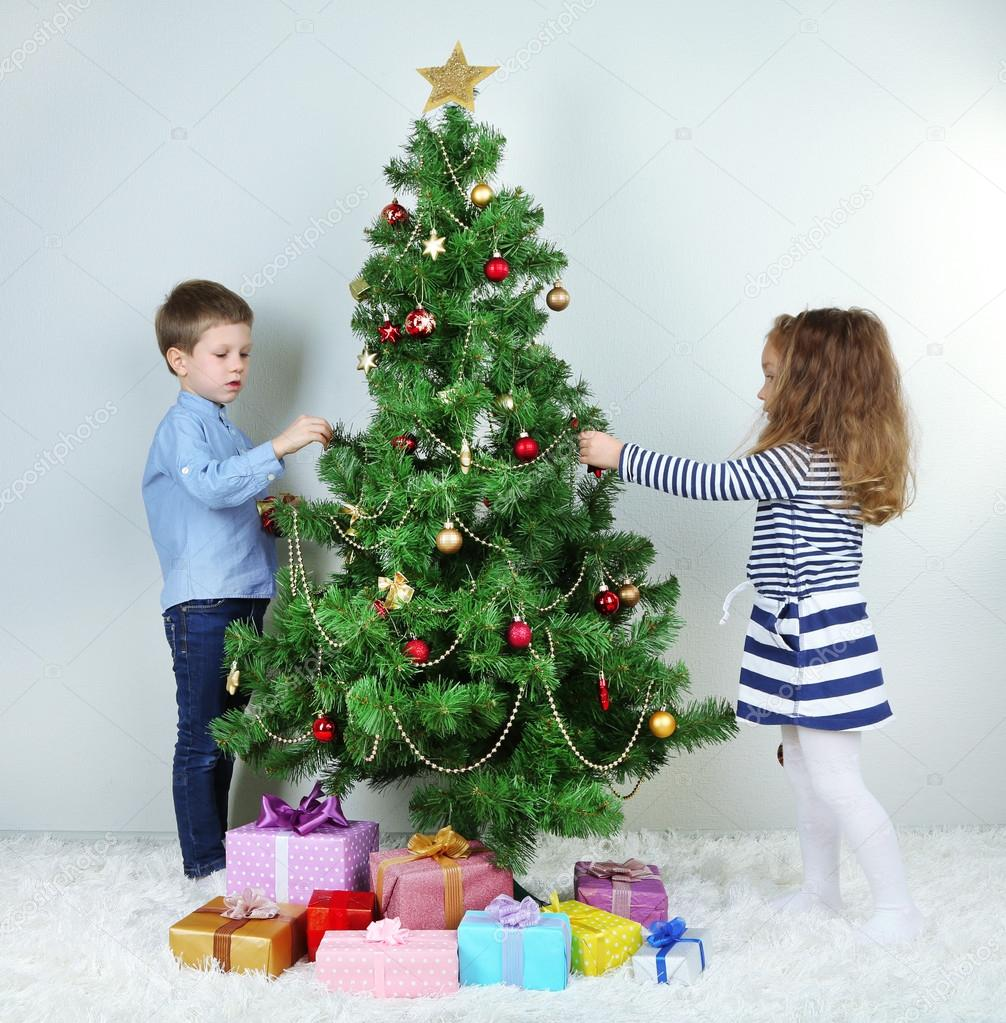 Kids Decorating For Christmas kids decorating christmas tree with baubles in room — stock photo