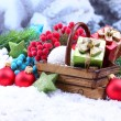 Composition with Christmas decorations in basket, fir tree on light background — Foto de Stock