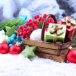 Composition with Christmas decorations in basket, fir tree on light background — Stock fotografie