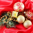 Beautiful Christmas decor on red satin cloth — Stock Photo #36377221