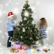 Kids decorating Christmas tree with baubles in room — Stock Photo #36377497