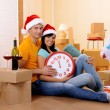 Young couple with boxes in new home celebrating New Years — Stock Photo #36377781