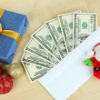 Dollar bills in envelope as gift at New year on wooden table close-up — Stock Photo #36377867