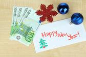 Euro banknotes as gift at New year on wooden table close-up — Stock Photo