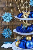 Soporte de adornos navideños en postre, sobre fondo de madera color — Foto de Stock