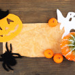 Old paper with Halloween decorations on grey wooden background — Stock Photo #36385519