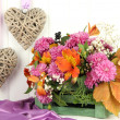 Flowers composition in crate with decorative hearts on table on wooden background — 图库照片