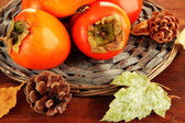 Ripe persimmons with bumps on wicker stand on wooden background — 图库照片