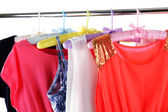 Beautiful dresses hanging on hangers isolated on white — Stock Photo