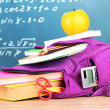 Purple backpack with school supplies on wooden table on green desk background — Stock Photo #36428127