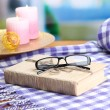 Stock Photo: Composition with old book, eye glasses, candles and plaid on bright background
