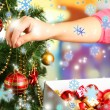 Decorating Christmas tree on bright background — Stock Photo