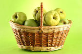 Sweet quinces in basket, on green background — Stock Photo