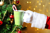 Santa holding mug in his hand, on bright background — Stock Photo