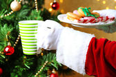 Santa holding mug and plate with cookies in his hand, on bright background — Stock Photo