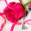 Beautiful pink rose with heart pendant — Stock Photo #36484031