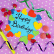 Card Happy Birthday surrounded by festive elements on purple background — Stock Photo