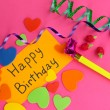 Card Happy Birthday surrounded by festive elements on pink background — Stock Photo