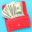 Purse with hundred dollar banknotes, on color background — Stock Photo