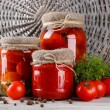 Tasty canned and fresh tomatoes on wooden table — Photo
