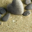 Stock Photo: Grey stone in shape of heart, on sand background