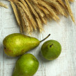 Stock Photo: Pears and sheaf on wooden background
