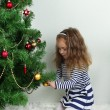 Little girl decorating Christmas tree with baubles in room — 图库照片