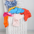 Full laundry basket  on wooden floor on gray background — Stock Photo