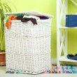Full laundry basket  on wooden floor on  home interior background — Stock Photo