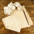 Stock Photo: Crumpled paper balls with ink pen and envelopes on wooden background