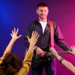 Stock Photo: Guitarist singing on stage at rock concert for his adoring fans