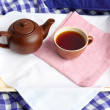 Cup and teapot on wooden tray on fabric background — Stock Photo