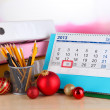 Table with office supplies, calendar and Christmas tinsel close-up — Stock Photo