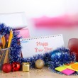 Table with office supplies, calendar and Christmas tinsel close-up — Stock Photo #36487325