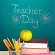 School supplies on blackboard background with inscription Teacher Day — Stock Photo