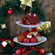 Christmas decorations on dessert stand, on wooden background — Foto de Stock